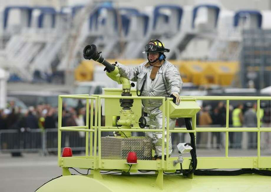 A firefighter waits at the ready for Boeing's new 747-8 to make its first flight at Paine Field in Everett. The flight was delayed for hours because of weather. Photo: Joshua Trujillo, Seattlepi.com