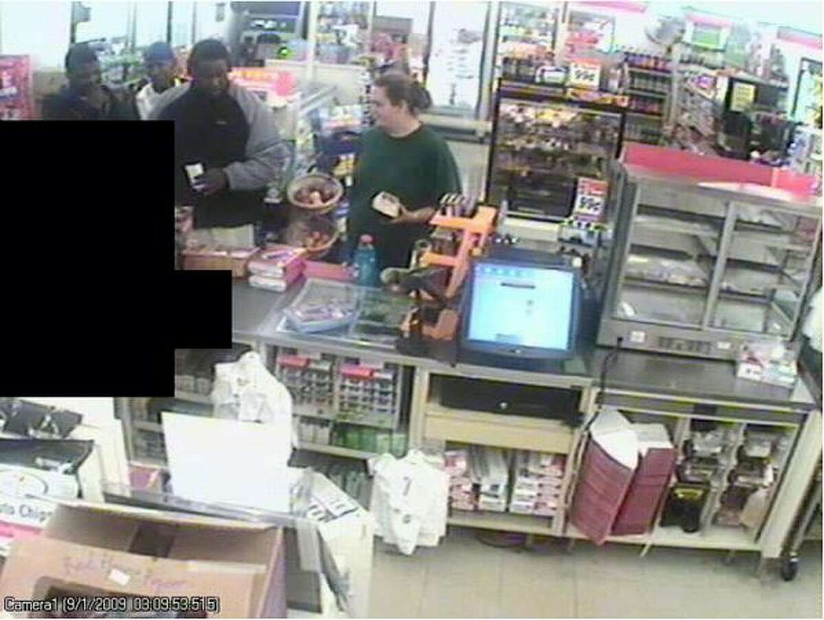 This Sept. 1 surveillance image shows the three men police suspect in a string of recent robberies. The woman accompanied the men at the convenience store, which police said was not robbed. A clerk is blacked out. (Seattle Police Department photo)