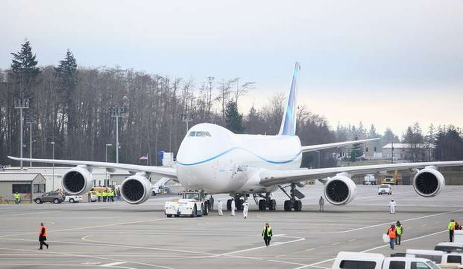 Boeing's new 747-8 is pulled by a tug from its parking stall before its first flight at Paine Field in Everett. Photo: Joshua Trujillo, Seattlepi.com
