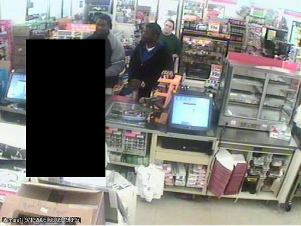This Sept. 1 surveillance image shows two of the three men police suspect in a string of recent robberies. The woman accompanied the men at the convenience store, which police said was not robbed. A clerk is blacked out. (Seattle Police Department photo)