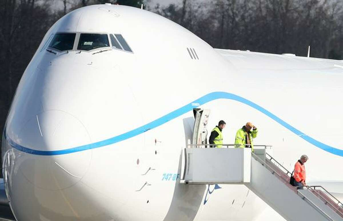 Workers exit Boeing's new 747-8 before takeoff for the plane's first flight.