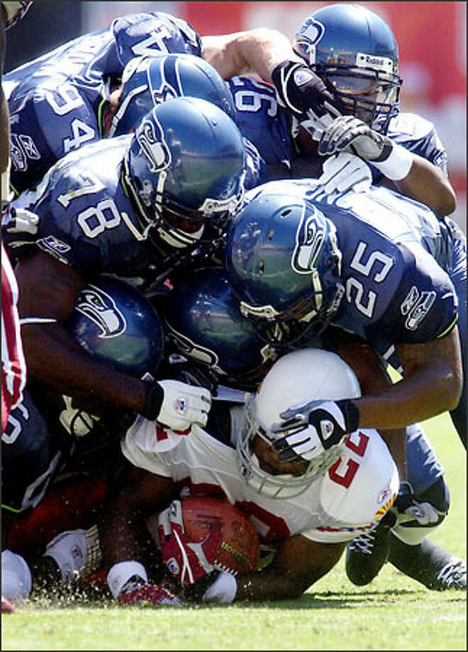 The Seahawks defense -- led by Reggie Tongue, Antonio Cochran, Chad Brown, Ken Hamlin and Norman Hand -- crush Arizona's Emmitt Smith. Photo: Associated Press