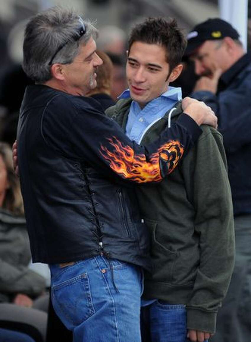 Jake Harris is greeted by one his fathers' best friend's during the public memorial service for the late 'Deadliest Catch' star Captain Phil Harris at the Smith Cove Cruise Terminal at Pier 91 in Seattle April 30, 2010.