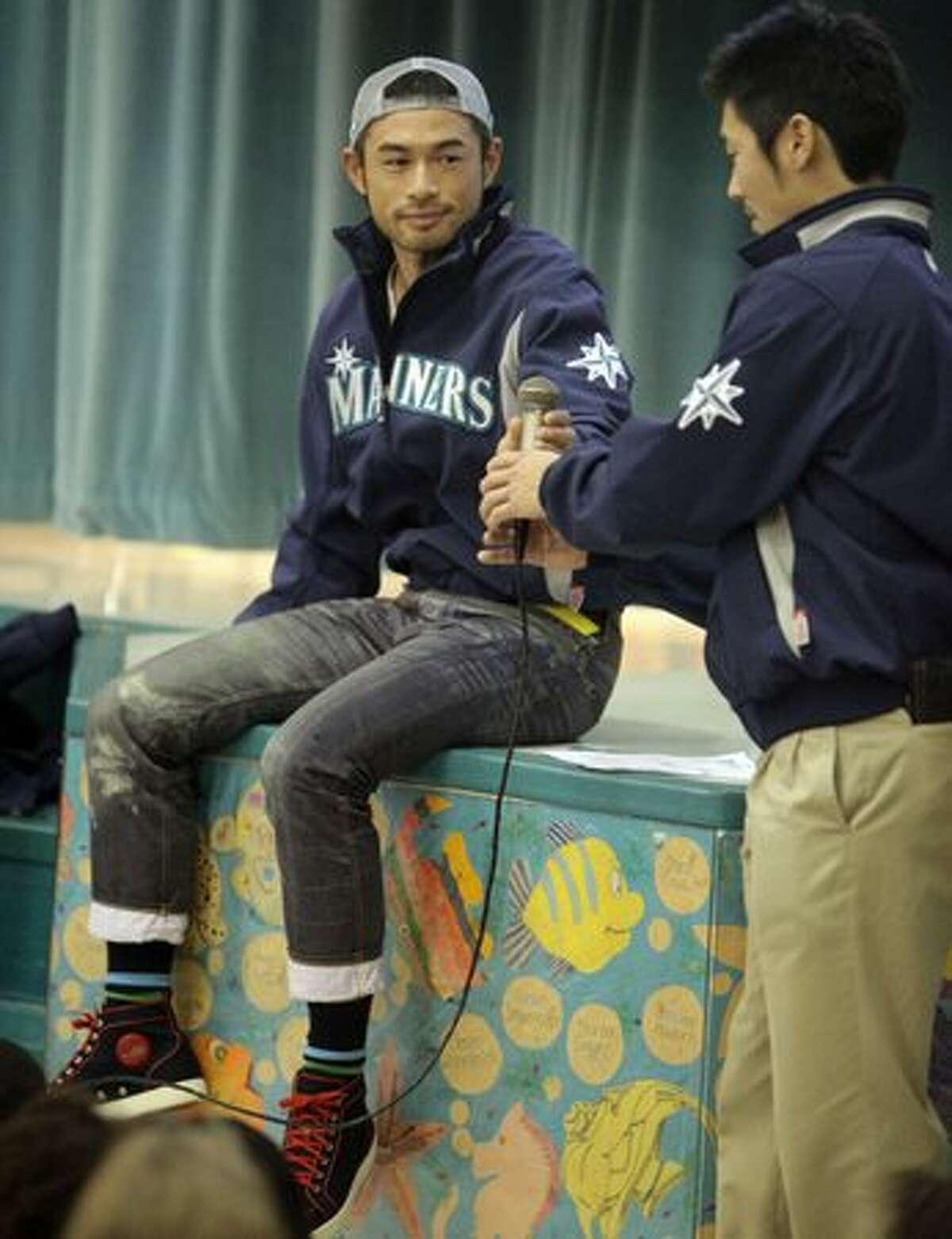 Seattle Mariners player Ichiro Suzuki hands off the mic to interpreter Antony Suzuki during a visit by members of the team to Lakeridge Elementary School in Seattle.