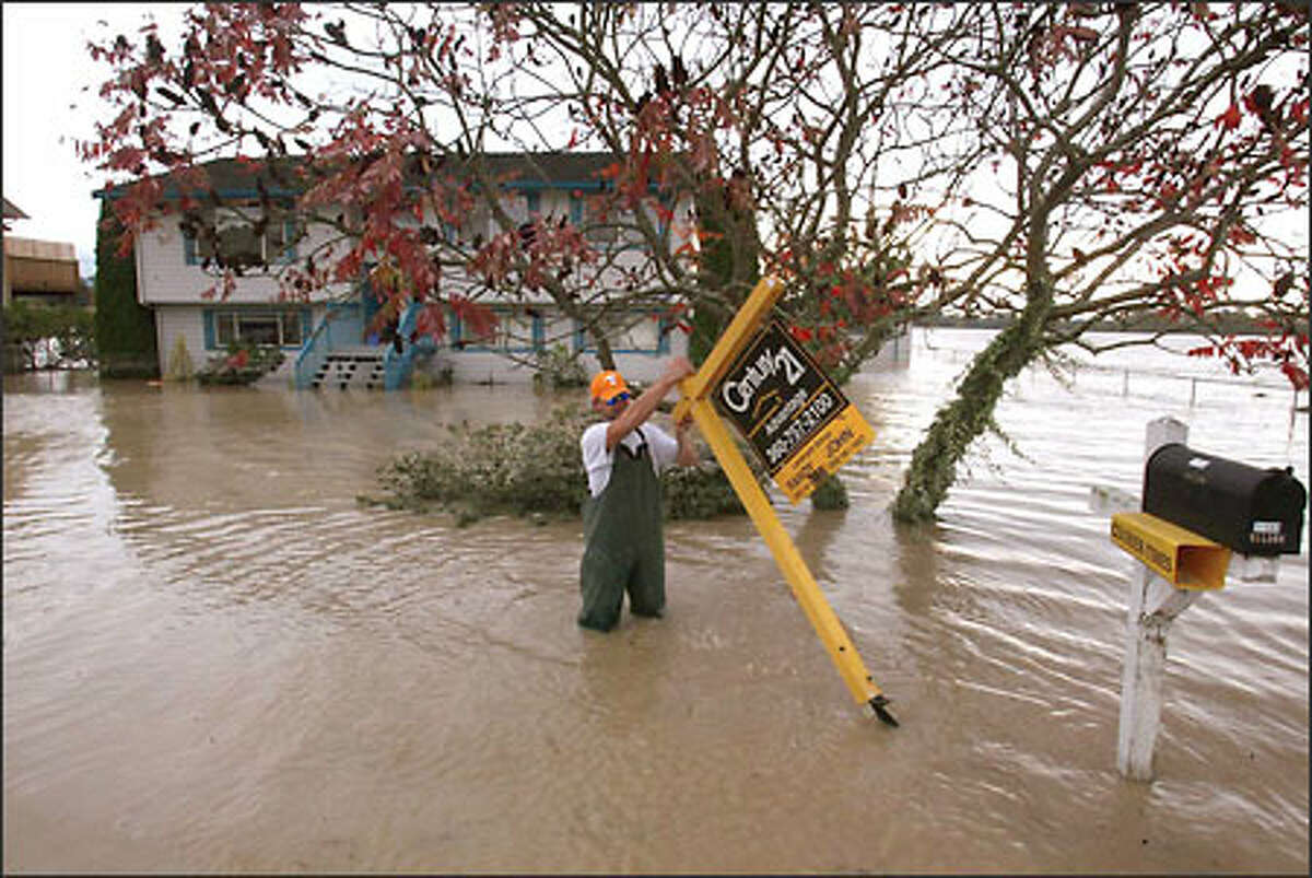 Tim Wilson recovers a for-sale sign from the water as he revisits his flood-damaged home on Lafayette Road in Skagit County, between Burlington and Sedro Woolly. Wilson's family was selling the house in preparation for a move to Tennessee.