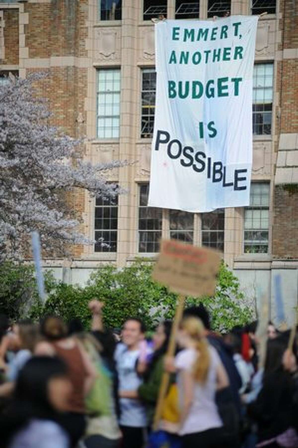 UW student activists hang a banner from the third-floor windows of the Art Building.