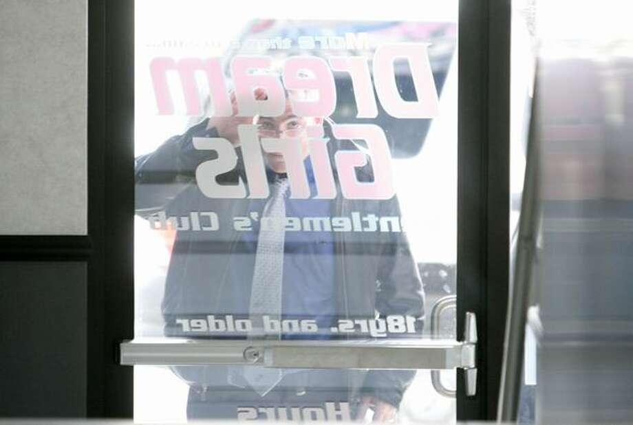 A passerby peeks into the front doors of Dream Girls, the Déjà Vu chain's newest strip club at 1530 First Avenue South. Photo: Joshua Trujillo, Seattlepi.com / seattlepi.com