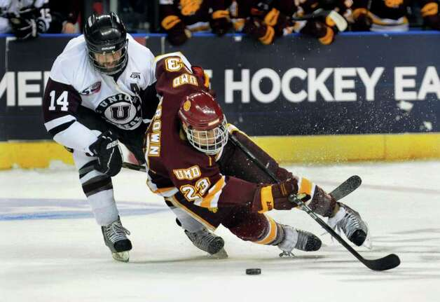 Minnesota Duluth's #23 J.T. Brown takes as spill as he and Union College's #14 Andrew Buote chase the puck, during NCAA hockey tournament action at the Webster Bank Arena at Harbor Yard in Bridgeport on Wednesday March 25, 2011. Photo: Christian Abraham / Connecticut Post