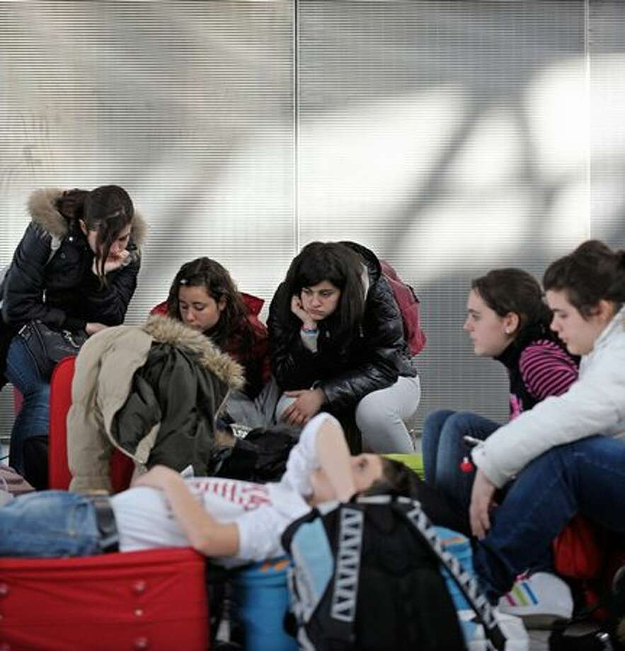 Young passengers sit on the floor while awaiting information about flight cancellations in Terminal 5 at Heathrow Airport, west of  London on April 15, 2010. No flights will be allowed into British airspace from 1100 GMT until at least 1700 GMT Thursday due to an ash cloud from a volcanic eruption in Iceland, air traffic control services announced. (ADRIAN DENNIS/AFP/Getty Images)