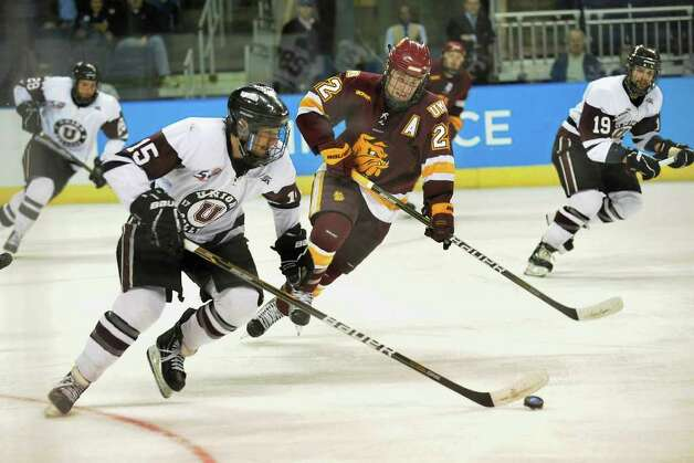 Union College's #15 Matt Hatch turns the puck around as Minnesota Duluth's #22 Mike Connolly comes in to intercept, during NCAA hockey tournament action at the Webster Bank Arena at Harbor Yard in Bridgeport on Wednesday March 25, 2011. Photo: Christian Abraham / Connecticut Post