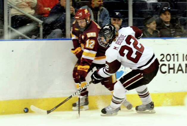 Union College's #22 Matt Bodie, right, and Minnesota Duluth's #12 Jack Connolly chase down the puck, during NCAA hockey tournament action at the Webster Bank Arena at Harbor Yard in Bridgeport on Wednesday March 25, 2011. Photo: Christian Abraham / Connecticut Post