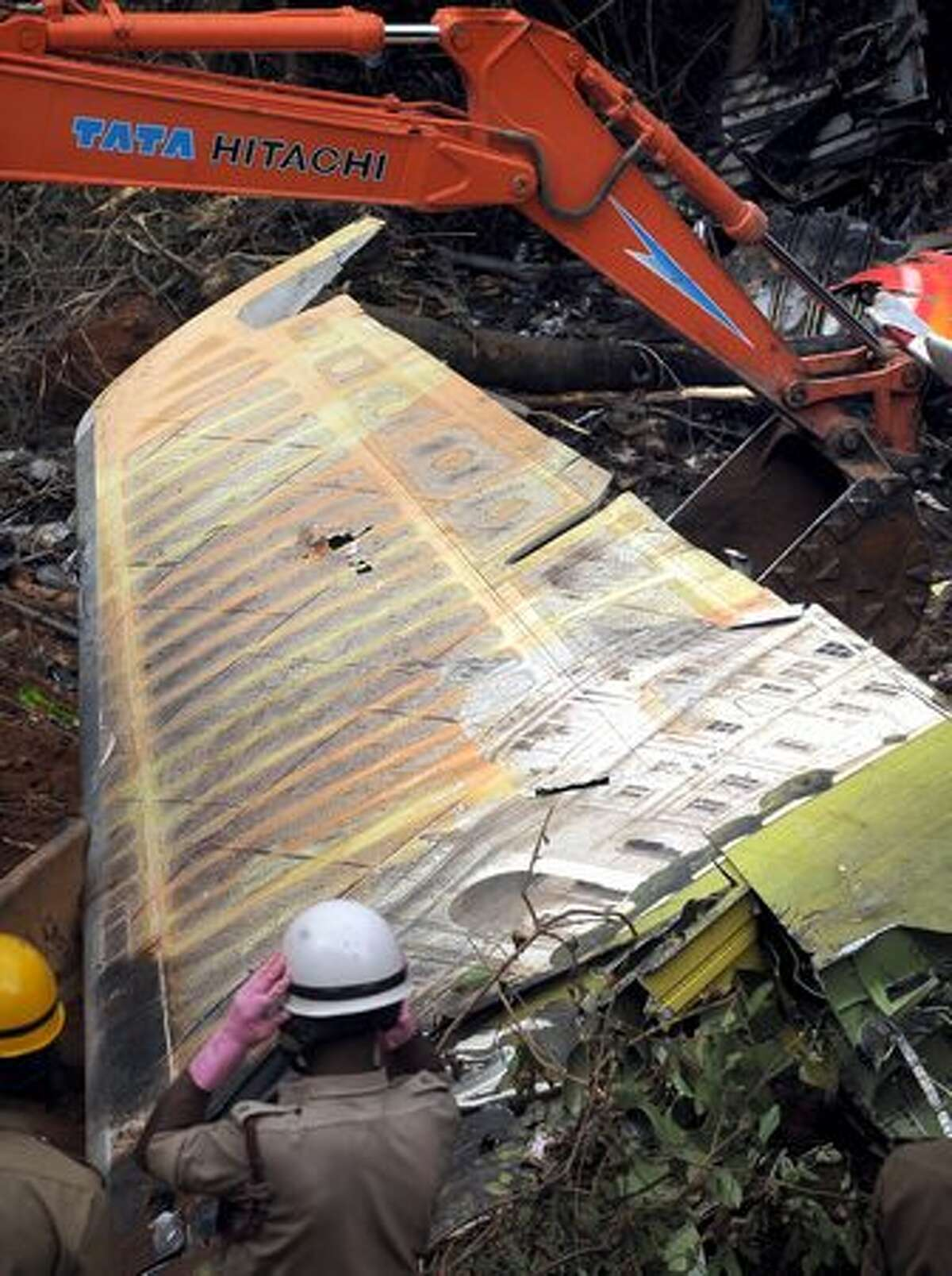 """Indian firefighters work at the plane crash site of the Air India Express Boeing 737-800 in Mangalore. Investigators combed the wreckage of an Air India Express jet that crashed into a forested gorge with the loss of 158 lives, searching for the """"black box"""" data recorder."""