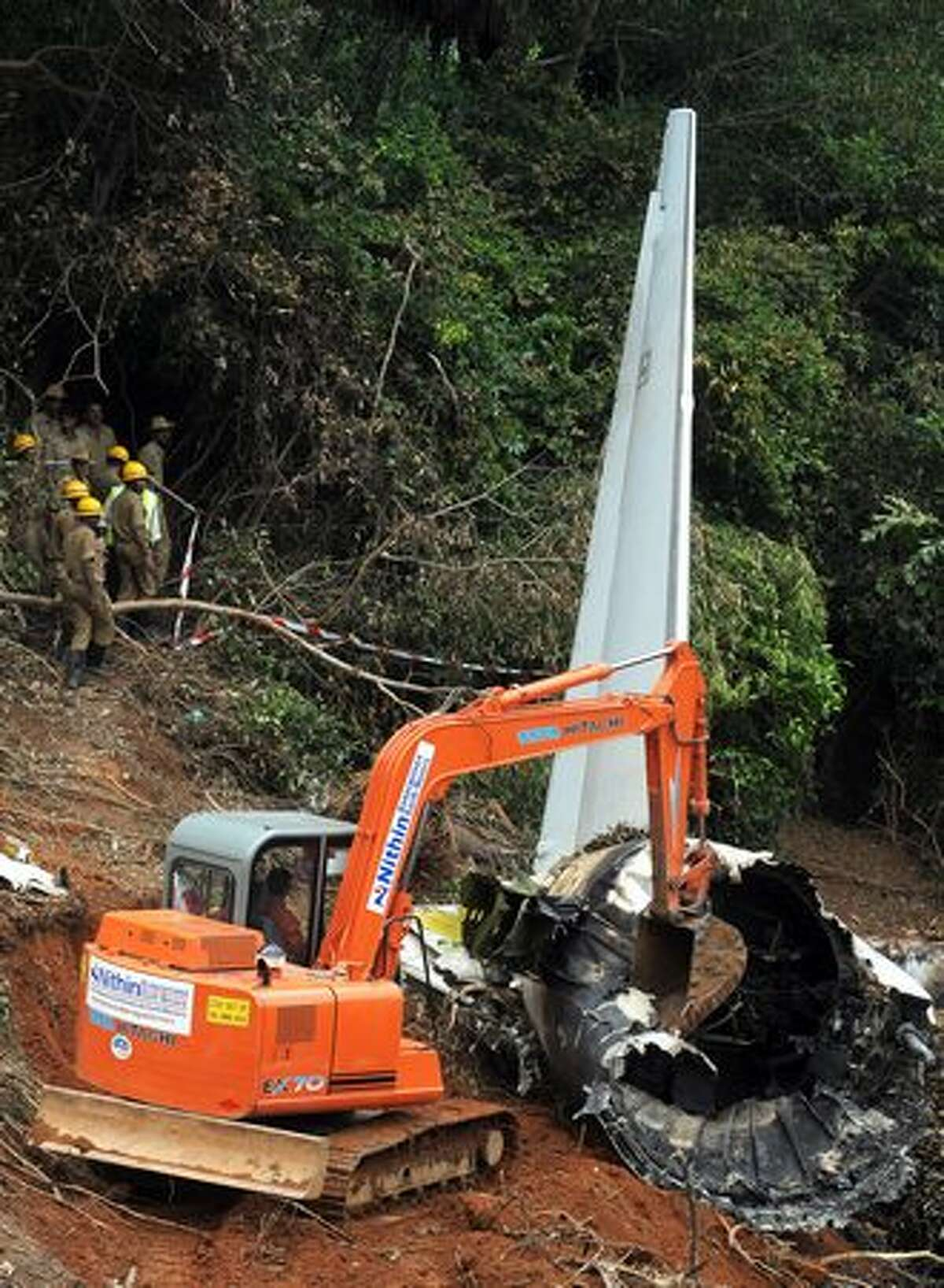 """An earth mover removes debris at the plane crash site of the Air India Express Boeing 737-800 in Mangalore. Investigators combed the wreckage of an Air India Express jet that crashed into a forested gorge with the loss of 158 lives, searching for the """"black box"""" data recorder."""