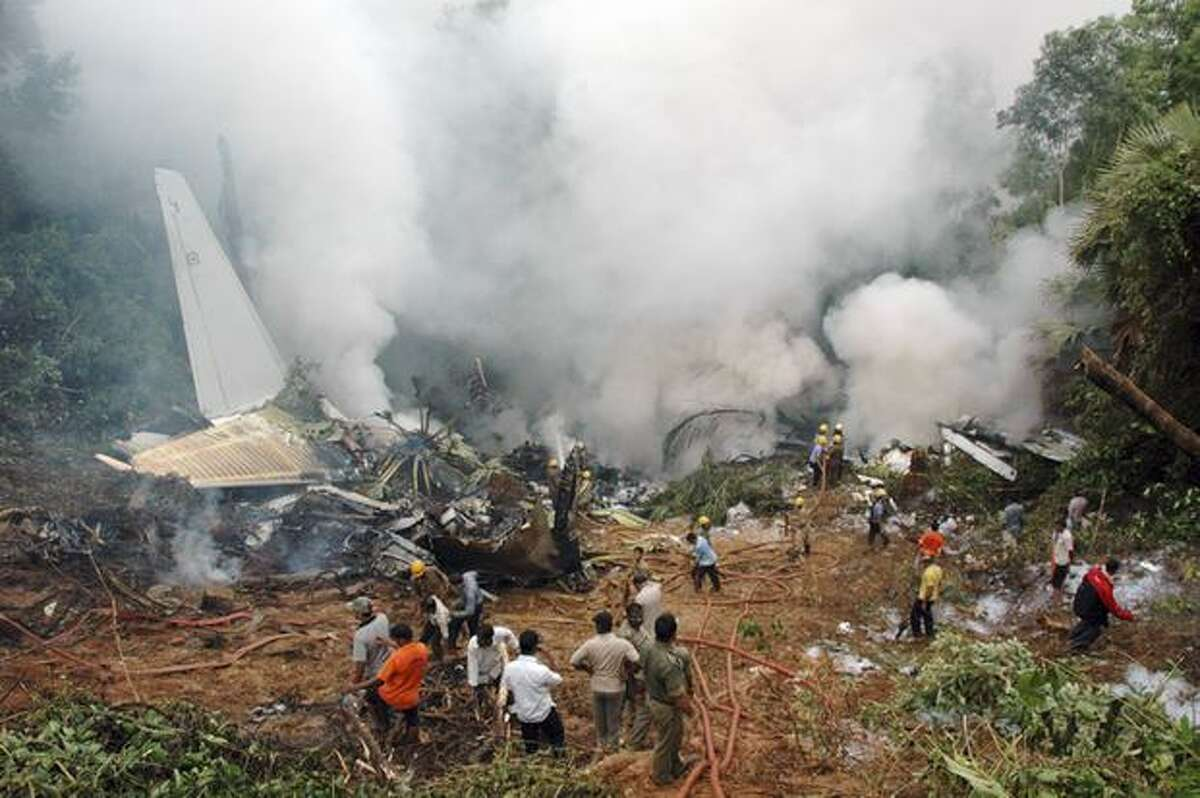 Rescue personnel are seen among the smoldering wreckage of an Air India Boeing 737-800 aircraft which crashed upon landing in Mangalore, India.