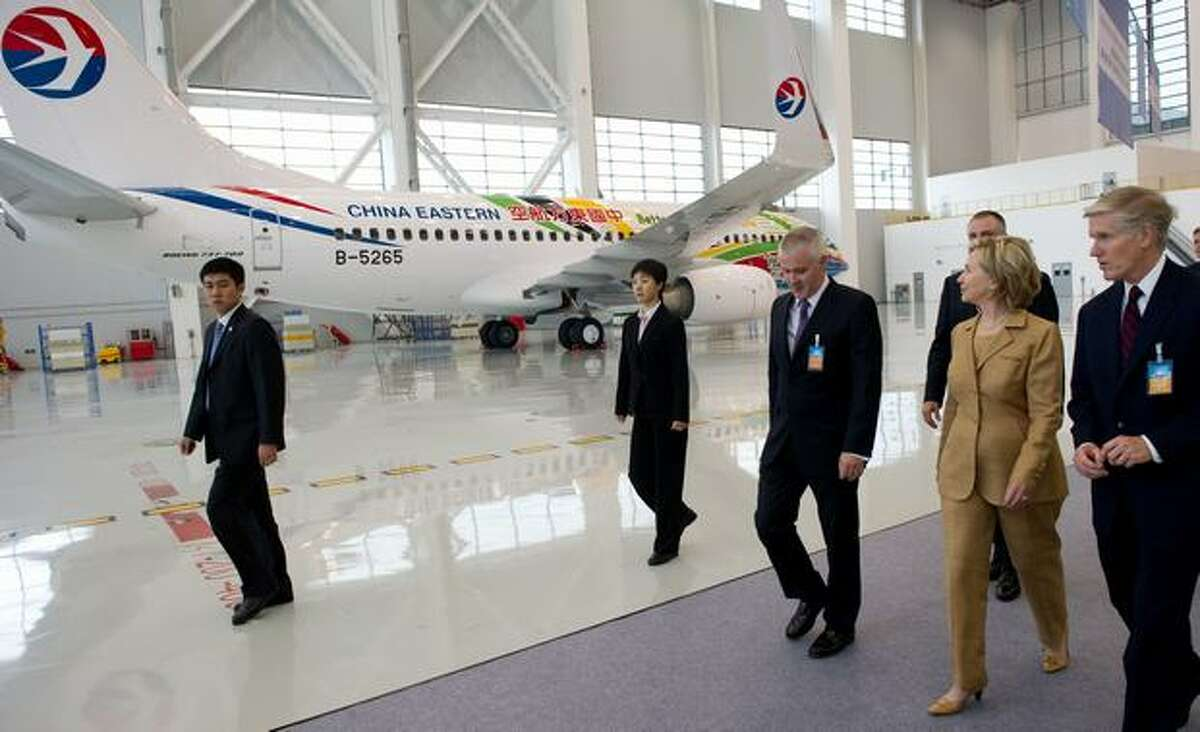 U.S. Secretary of State Hillary Clinton looks at a Boeing 737 airplane as she walks alongside Boeing International President Shephard Hill (right) after speaking on commercial development at the Boeing Maintenance Facility at Pudong International Airport in Shanghai.