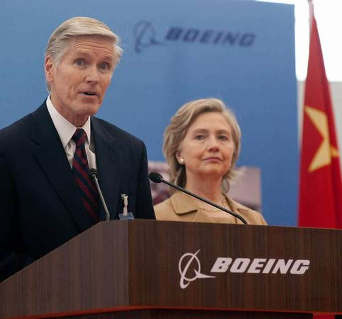 Boeing International President Shephard Hill (left) speaks alongside U.S. Secretary of State Hillary Clinton at the Boeing Maintenance Facility at Pudong International Airport in Shanghai.