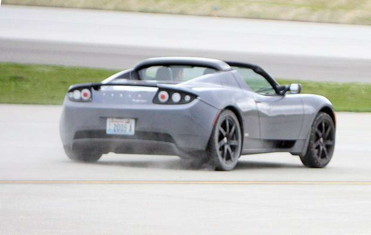 A visitor drives an electric Tesla Roadster on the taxiway outside the Future of Flight Aviation center, at Snohomish County's Paine Field.