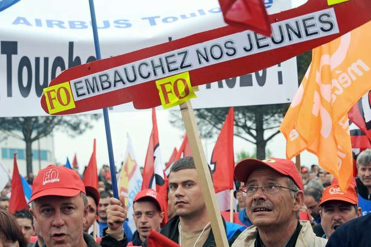 Airbus employees demonstrate in Toulouse, France, in front of the entrance of their company to ask for better raises. The banner in the center reads