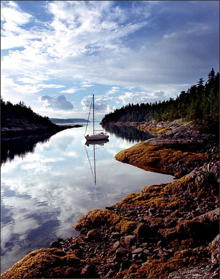 The chartered 38' yacht Tradewinds sails at dawn in the Copeland Islands in Desolation Sound, B.C.