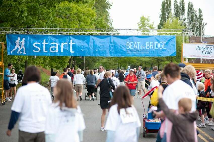 Participants gather outside of Husky Stadium to register and warm up before the annual Beat the Bridge fundraiser on Sunday, May 16, 2010 in Seattle.