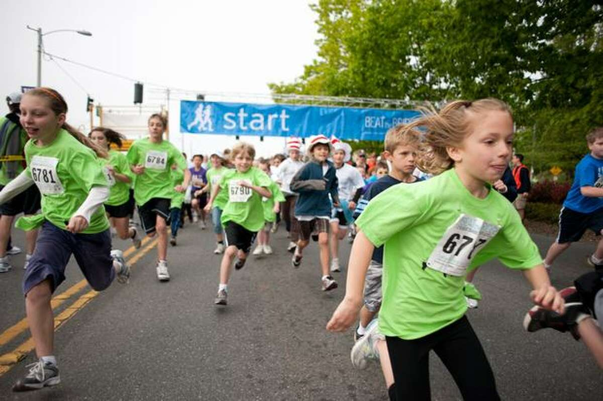 Children sprint off the starting line as the signal is given.