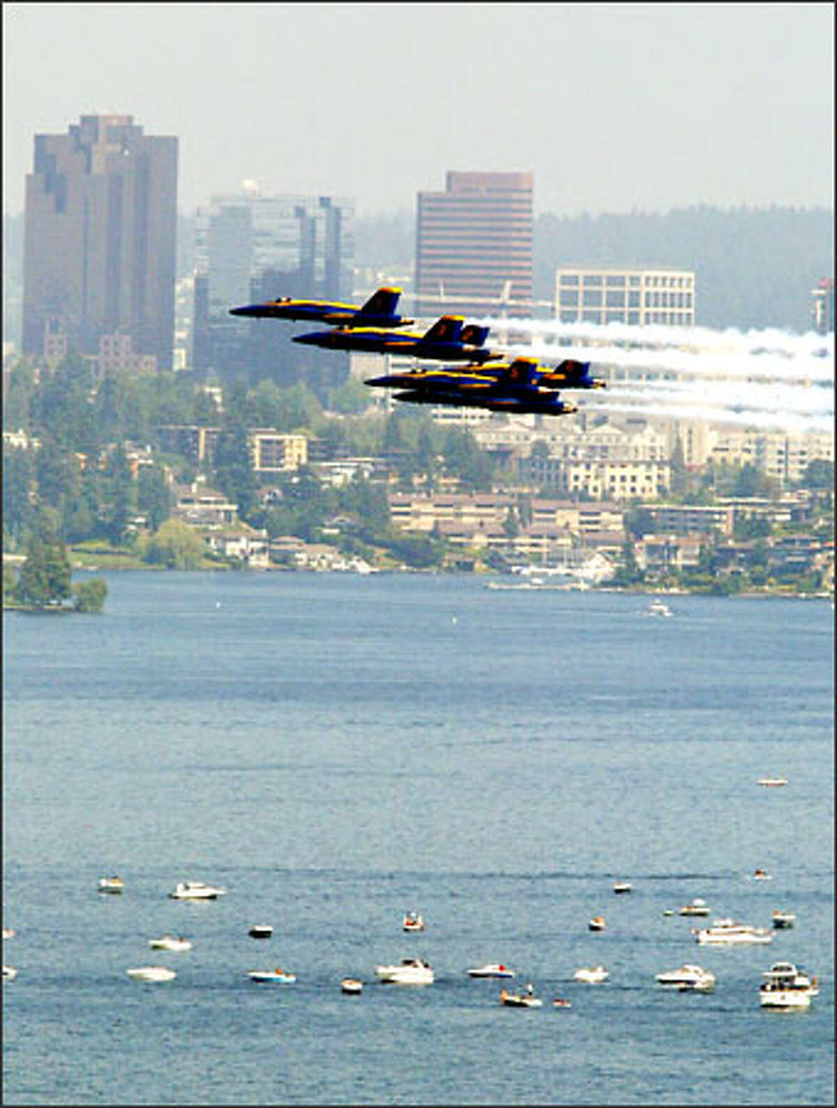 With Bellevue in the distance and Lake Washington below, the Blue Angels scream past during a practice run yesterday. Interstate 90 will close several times through Sunday for the Navy fliers' practices and performances as part of Seafair.