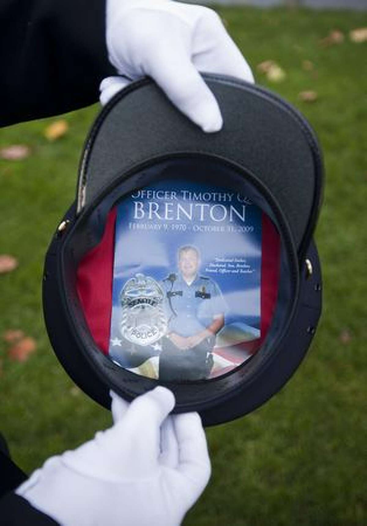 A Canada Border Services officer displays a program in her hat from the memorial service for Timothy Brenton at KeyArena in Seattle Friday following a memorial service for the slain police officer.