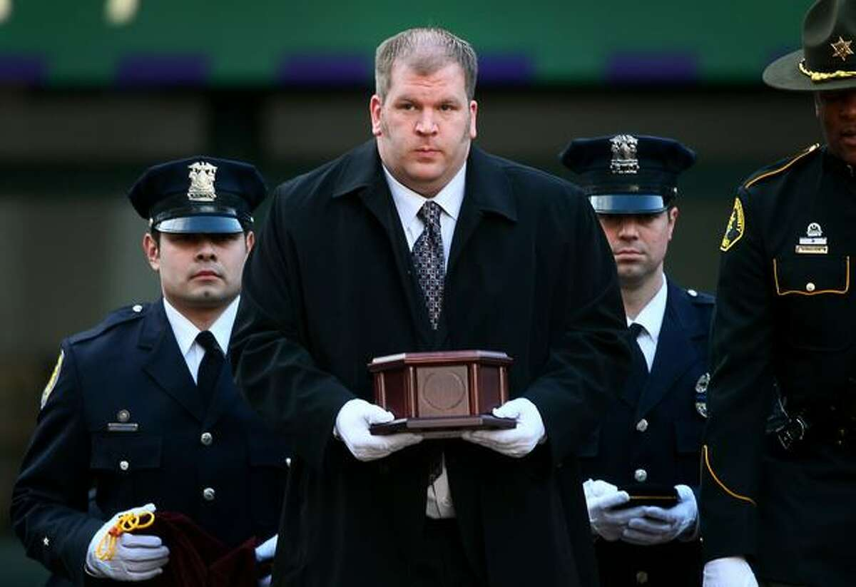 Seattle Police Officer Timothy Brenton's brother Matt carries his remains from KeyArena in Seattle, following a memorial service for the slain police officer.