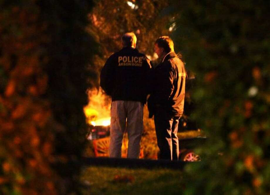 Arson and bomb squad officers arrive on the scene where a man was shot by police officers after he was investigated as a person of interest in the killing of Seattle Police Officer Timothy Brenton. Photo: Joshua Trujillo, Seattlepi.com