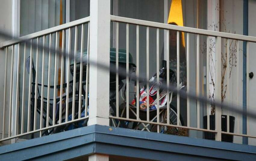 A woman peeks from her apartment as SWAT officers converge on the scene where a man was shot by police officers after he was investigated as a person of interest in the killing of Seattle Police Officer Timothy Brenton.