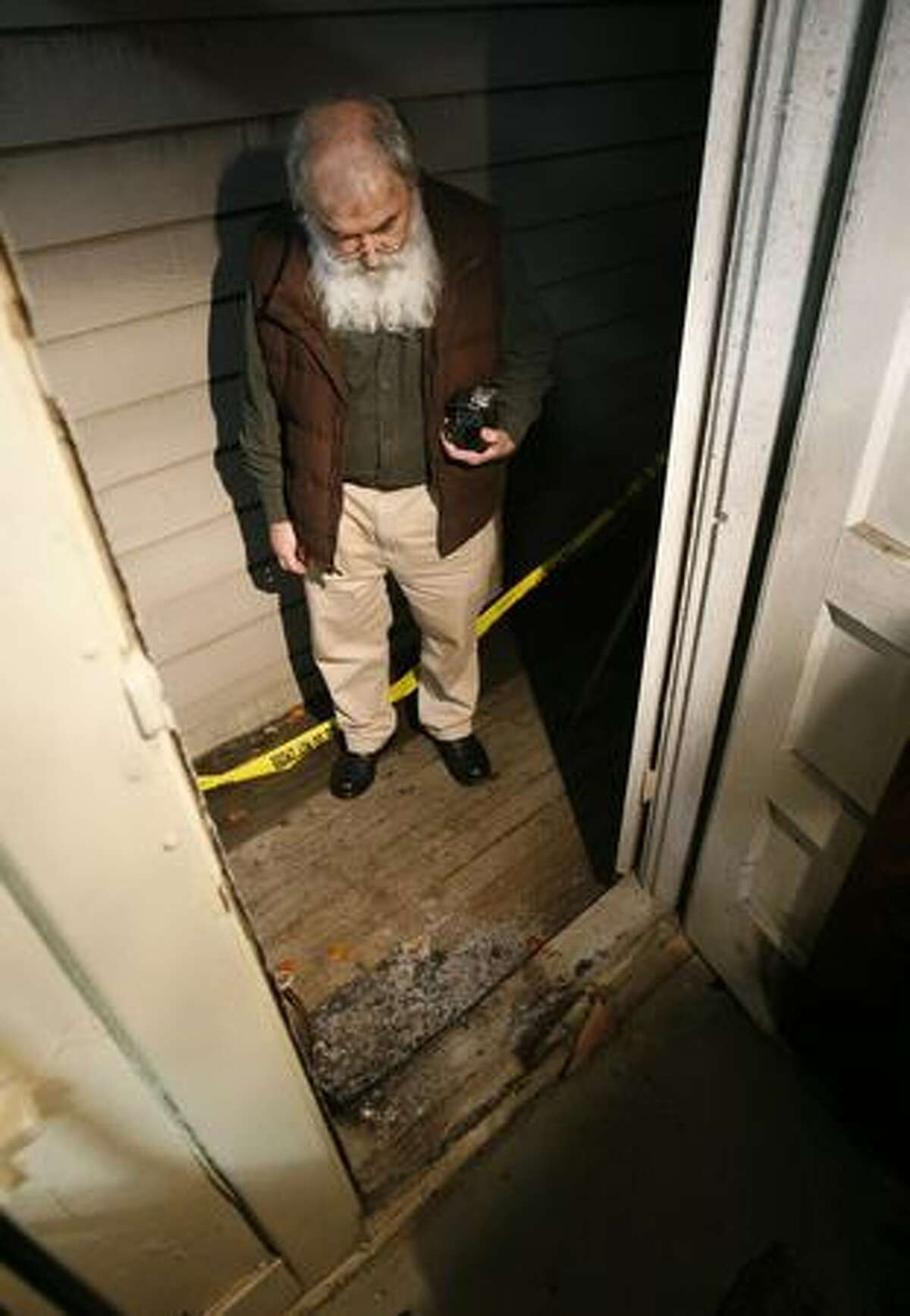 Bob Mullins, owner of Moonphoto, examines the area where an arsonist attempted to ignite his business on Sunday November 8, 2009.