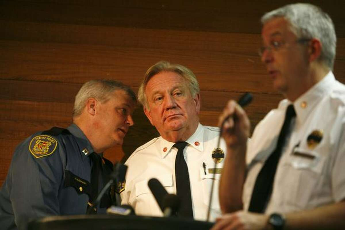 Acting Assistant Police Chief Chief Paul McDonagh, left, speaks with Assistant Fire Chief A.D. Vickery while Fire Marshall John Nelsen addresses some of the estimated 800 people gathered for one of two community meetings at Phinney Ridge Lutheran Church.