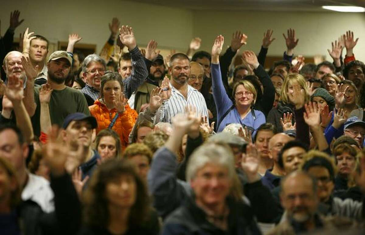 Some of the estimated 800 people who gathered Tuesday for the first of two community meetings at Phinney Ridge Lutheran Church raise their hands when asked if they have smoke detectors. The neighborhood had two meetings to discuss a rash of recent arsons that have the community on edge. Fourteen recent fires have been blamed on arson, one of the fires destroying three businesses and damaging others.