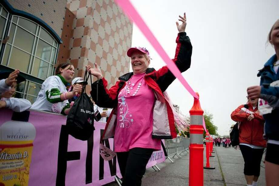 A woman is greeted at the finish line with cheers and high-fives during the 17th Annual Komen Puget Sound Race for the Cure in Seattle on June 6, 2010. Photo: Elliot Suhr, Seattlepi.com