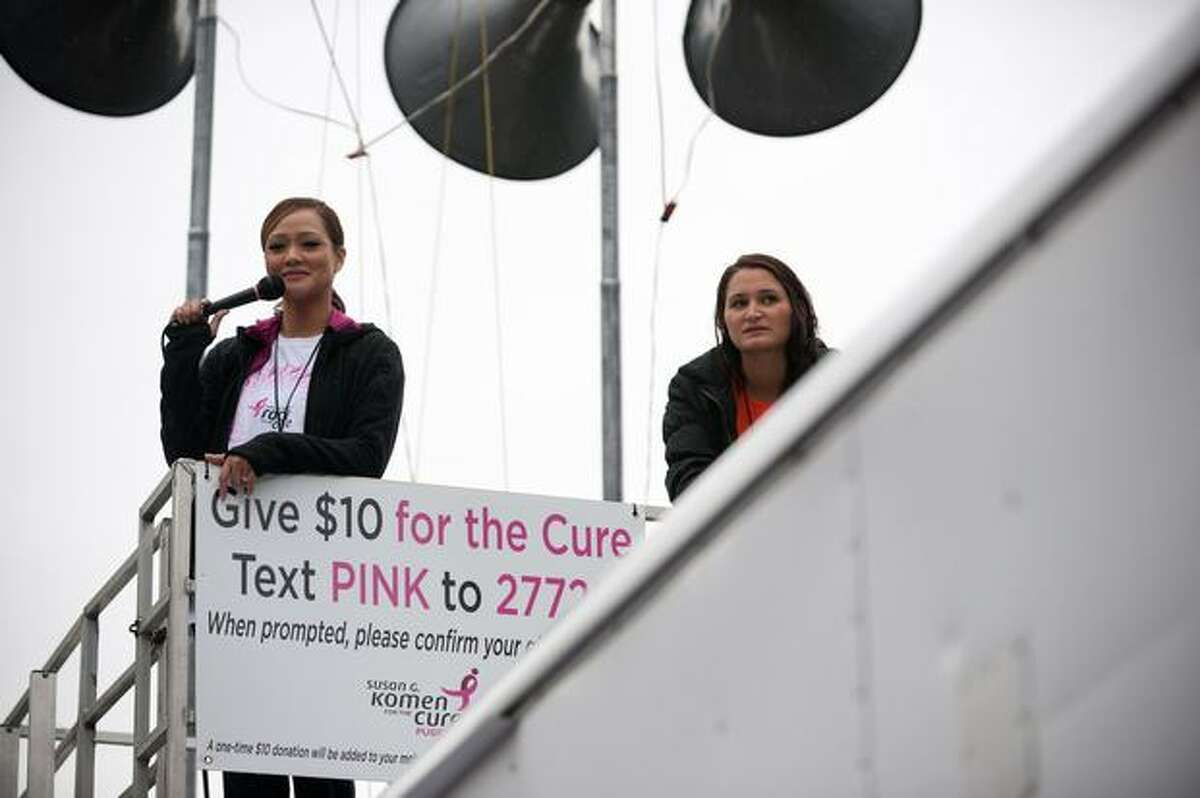 Two women from Q13 Fox News motivate and encourage runners as they cross the finish line during the 17th Annual Komen Puget Sound Race for the Cure in Seattle on June 6, 2010.