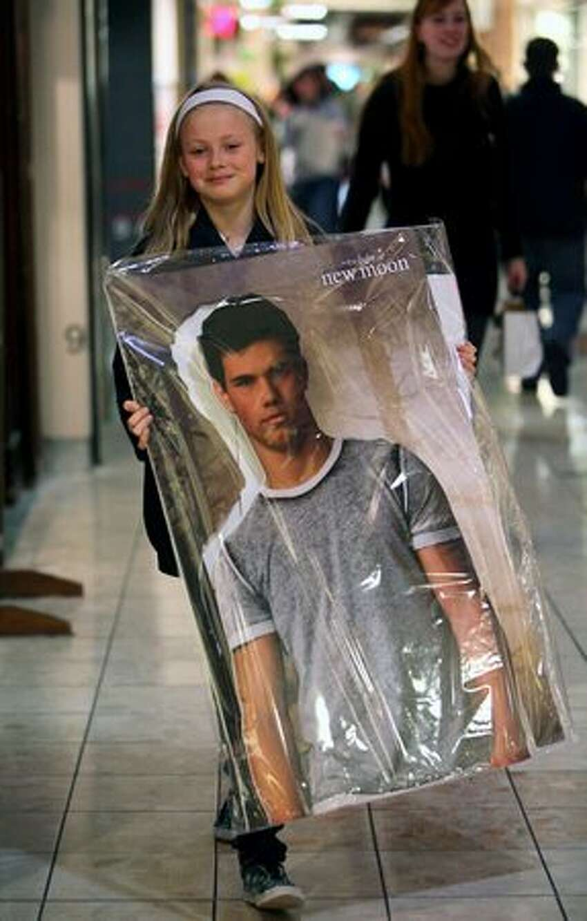 Alli Moore, 12, carries a poster of her favorite Twilight character, Jacob Black, played by actor Taylor Lautner. Lautner was not in attendance at the mall.