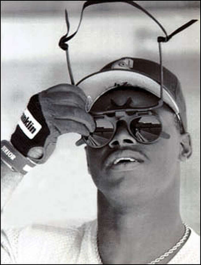 Ken Griffey Jr. checks out fielding sunglasses prior to a spring training game against the Milwaukee Brewers. Photo: Seattle Post-Intelligencer