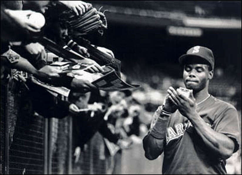 Ken Griffey Jr. signs autographs before a game.