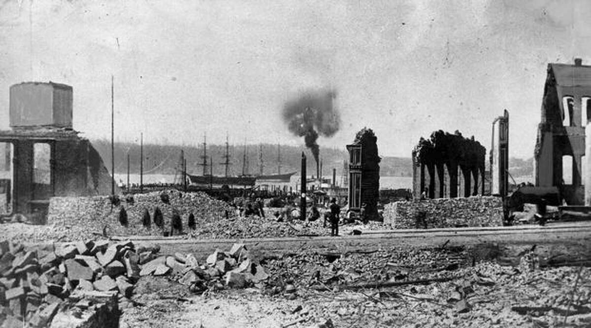 The aftermath of The Great Seattle fire, which occurred on June 6, 1889. The fire leveled the city's entire business district, 29 blocks of mainly flimsy wooden buildings. The fire also killed millions of waterfront rats. This picture was taken looking toward Elliott Bay from Front Street (now known as First Avenue), looking over where a row of waterfront warehouses once stood. Not a wharf or warehouse was left intact in the mile from Jackson Street to Union Street. A new city of more substantial brick buildings was quickly constructed.