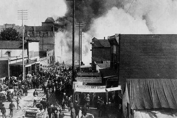 On June 6, 1889, a fire started from an spilled glue pot in a carpentry shop in a downtown Seattle building and quickly spread. Due to a woeful water system, coupled with a city constructed mainly with wood, the Great Fire destroyed Seattle's entire business district, 29 square blocks including the railroad terminals and nearly all of the city's wharves. Here a crowd helplessly watches the approaching flames during the beginning hours of the fire.