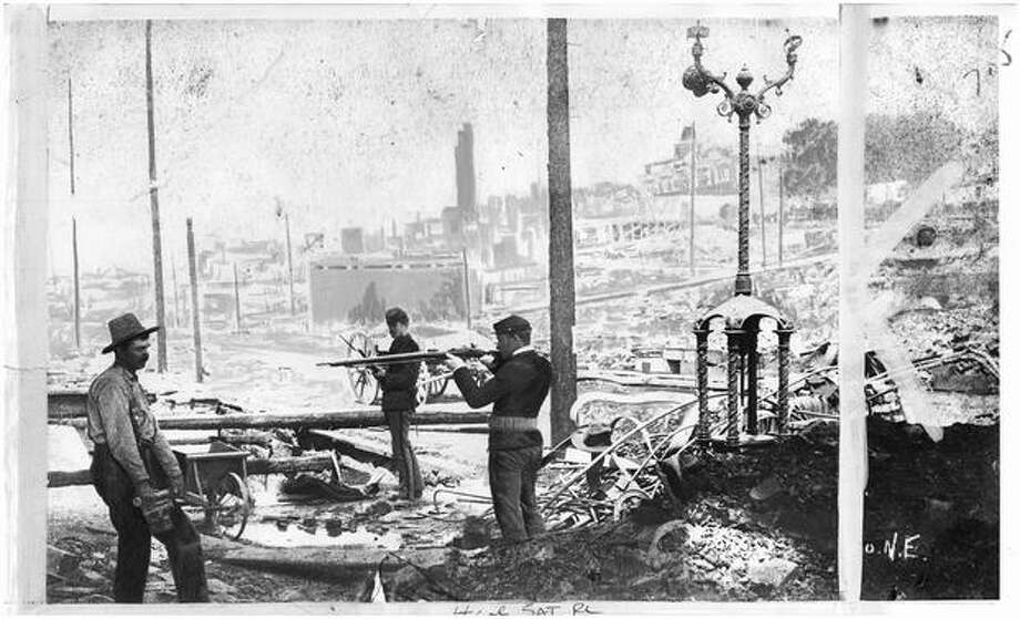 A scene of the cleaning up process after the Great Seattle Fire of 1889. The caption of this seattlepi.com archive photo says the man was a reluctant volunteer. This image here is believed to be near where Colman Dock is today. Photo: P-I File