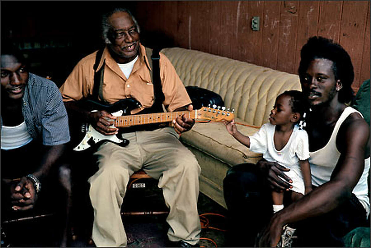 R.L. Burnside with his grandson Cedric Burnside, his great-granddaughter Shundrianna Jackson, and her stepfather, Mitchell Jackson, Holly Springs, Mississippi, 2000. © Annie Leibovitz