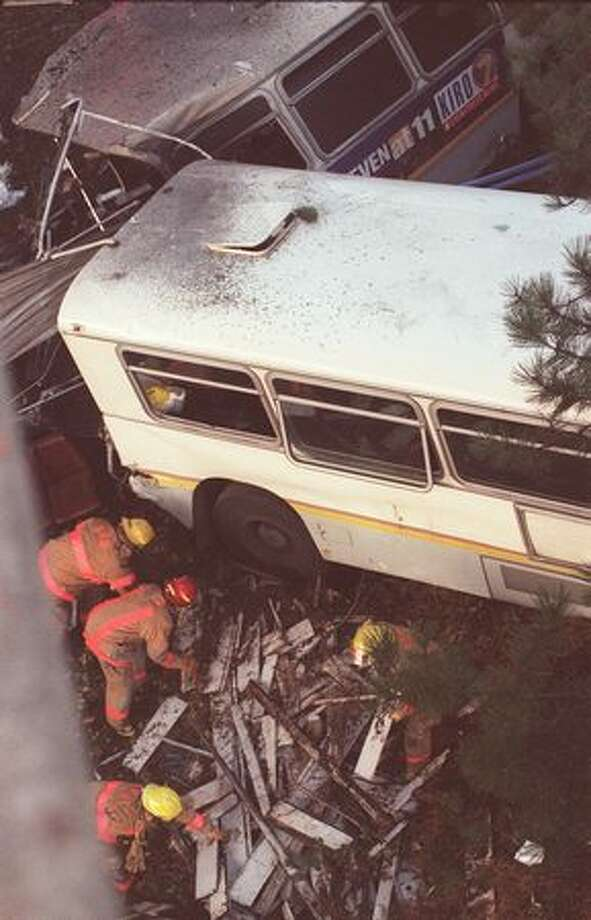 Firefighters look through debris for victims of a bus that drove off the Aurora Bridge on November 27, 1998. A gunman shot and killed driver Mark McLaughlin before killing himself. Thirty-three people were injured.  (Robin Layton/P-I) Photo: P-I File
