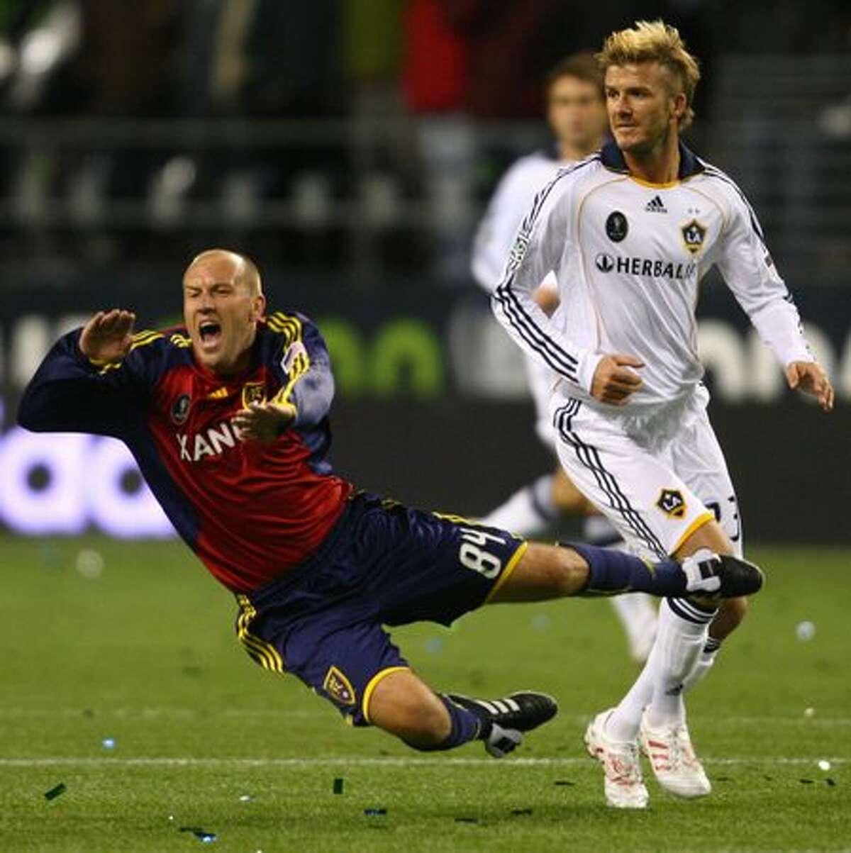 Real Salt Lake player Clint Mathis falls over LA Galaxy player David Beckham.