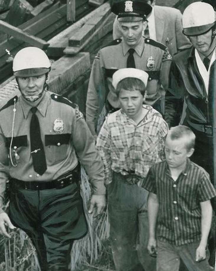 Three police patrolmen escort two boys away from the Aurora Bridge on July 17, 1957. (Photo by Mannery/P-I) Photo: P-I File