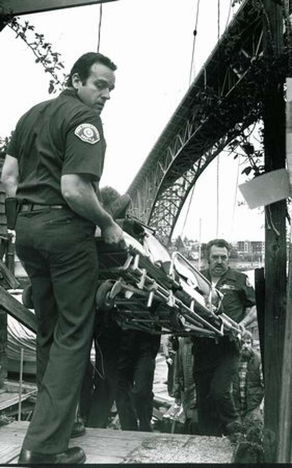 Firefighters carry Mary Warme on a stretcher up from Lake Union after she plunged from the Aurora Bridge and was rescued by two boaters on April 3, 1980. (Photo by Phil Webber/P-I) Photo: P-I File