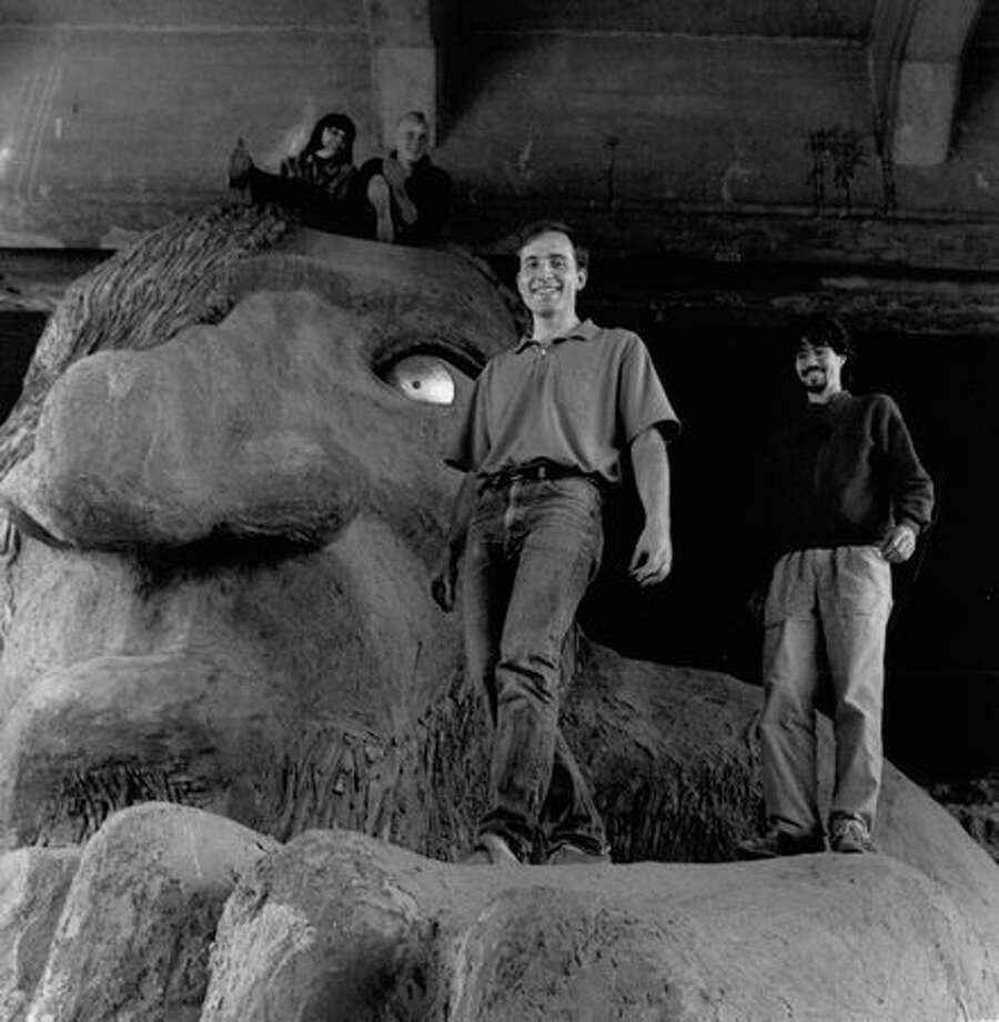 Will Martin and Ross Whitehead pose on the Fremont Troll, the newly beloved landmark they helped create on July 11, 1991, which is underneath the north side of the Aurora Bridge. (Photo by Phil Webber/P-I) Photo: P-I File