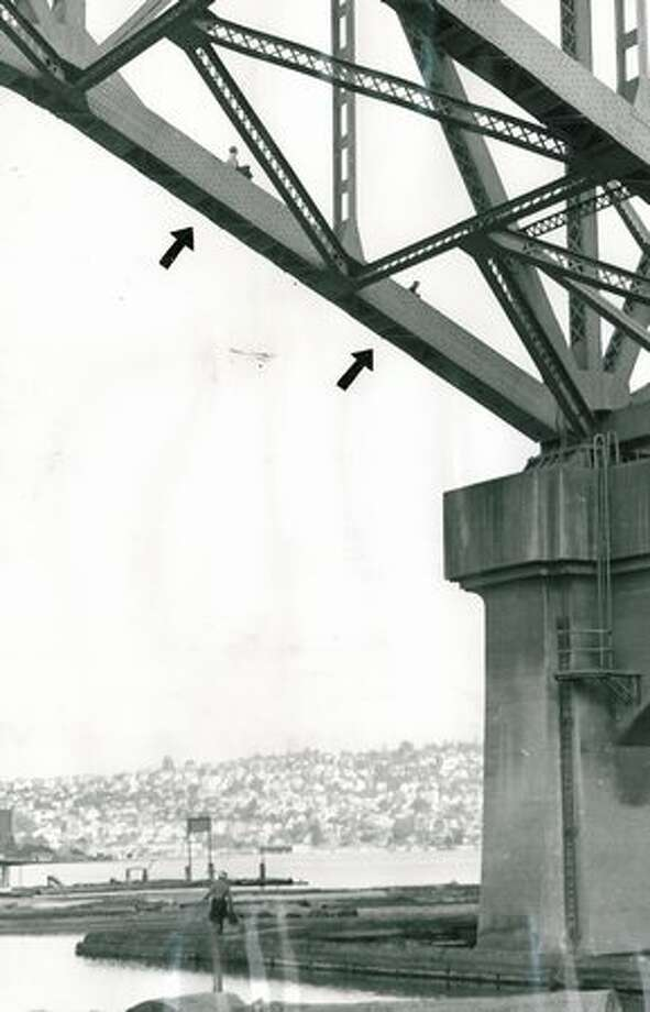 Arrows point to Melvin Olson, left, 14, and Robert Sandbom, 10, inching their way down by police request from a high girder of the Aurora Bridge on July 17, 1957. (Photo by Mannery/P-I) Photo: P-I File