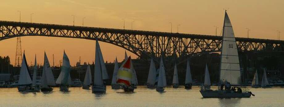 Sailboats compete during Duck Dodge on May 22, 2007 on Lake Union as dusk falls behind the Aurora Bridge in Seattle. (Photo by Joshua Trujillo/P-I) Photo: P-I File