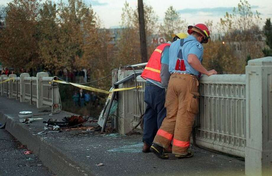 Firefighters look over the Aurora Bridge where a Metro bus drove off and landed on an apartment building down below on November 27, 1998. A deranged passenger shot and killed Metro bus driver Mark McLaughlin. The bus swerved through oncoming traffic, crashed through a guardrail, plunged 40 feet and split in half. The  gunman died and 33 people were injured.  (Robin Layton/P-I) Photo: P-I File